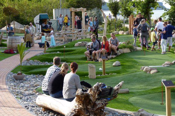 Besuchergruppe auf der Outdoor-Minigolfanlage im Ostseebad Göhren auf der Insel Rügen - Freizeitspaß für die ganze Familie direkt an der Ostsee - Spiel und Spaß für Groß und Klein